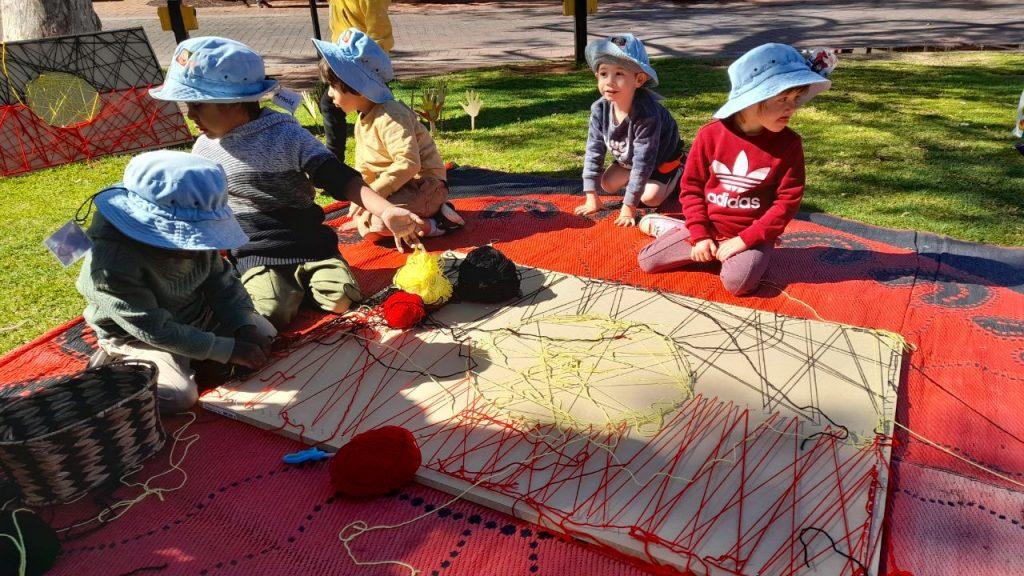 Children weaving an Aboriginal flag